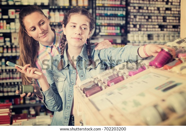 Cheerful woman and girl shopping color in glass jar in art store