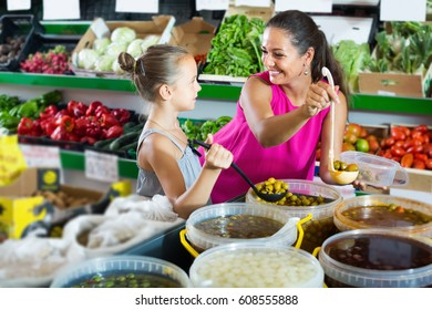 Cheerful woman with girl taking pickled olives from bucket in food store