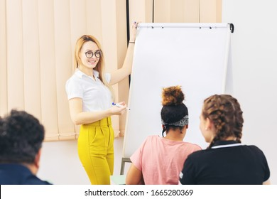Cheerful woman giving a presentation to multiracial people - Modern young trainer looking at international students during meeting – Personal development speech to colleagues