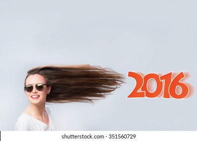 Cheerful woman with hair in the wind. Background of the text in 2016.