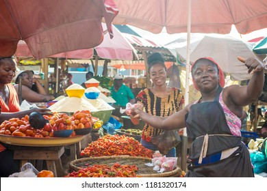 cheerful woman handing over some wrapped tomatoes to a customer in a local african market