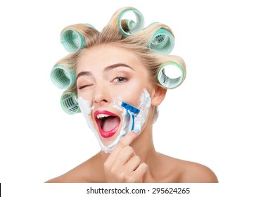 Cheerful woman has having cream over her face. She is shaving herself with razor. The girl is winking and laughing. Isolated on background and copy space in right side