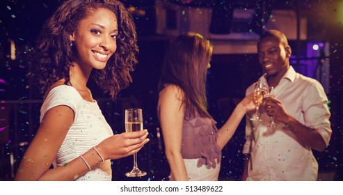 Cheerful woman having champagne and her friends toasting glasses against flying colours