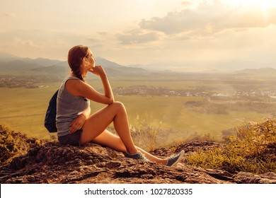 Cheerful woman is having rest on the edge of the cliff and looking at the sun valley and mountains.