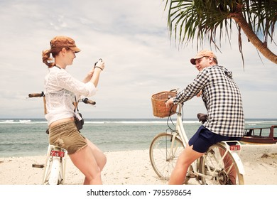 Cheerful woman is having taking pictures her boyfriend in the coast with old fashioned bicycle. Enjoying the company of each other forever.