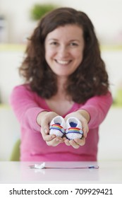 cheerful woman holding baby bootees for a gay maternity family