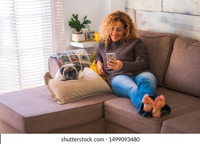 Cheerful woman at home lay down on the sofa with smart phone  mobile device and nice lazy dog pug near her - concept of real life and friendship with animals