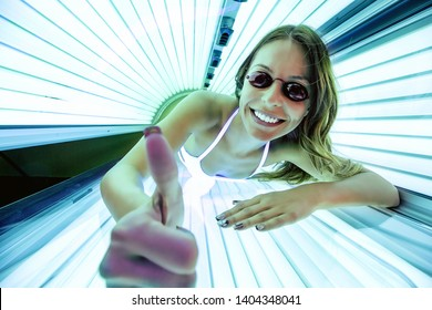 Cheerful woman inside of a sunbed smiling and enjoying