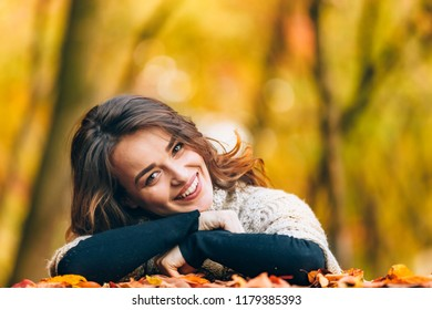 cheerful woman with leaned head to the side smiles on the background of autumn landscape