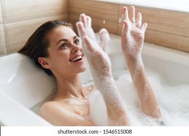cheerful woman lies in bathtub rest lifestyle spa treatments hygiene