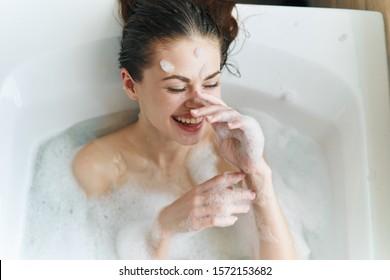 A cheerful woman lies in a clean skin bath spa relaxation treatments