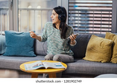 Cheerful woman listening to music with large headphones and singing.Enjoying listening to music in free time at home.Relaxing with music,happy woman singing.Positive mood