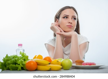 Cheerful woman is looking aside thoughtfully. She can not decide what should eat. Fruits and vegetables or donuts. The lady is sitting at the table. Isolated on a white background