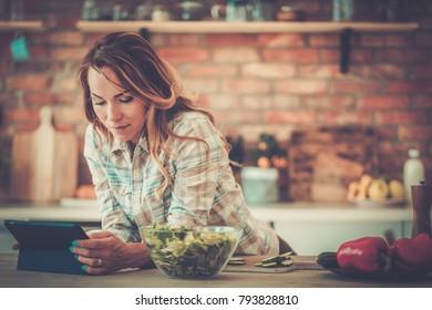 Cheerful woman looking online recipe.