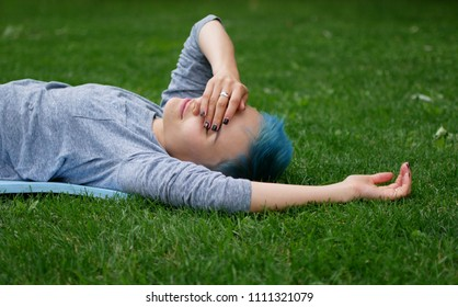 cheerful woman lying down on a grass and dreaming.