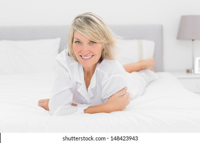 Cheerful woman lying on her bed at home in bedroom