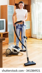Cheerful woman make cleaning at house using hoover