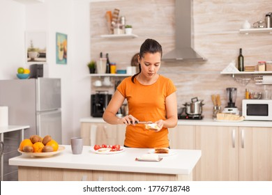 Cheerful woman in the morning spreading butter on roasted bread. Knife smearing soft butter on slice of bread. Healthy lifestyle, making morning delicious meal in cozy kitchen. Traditional tasty lunch