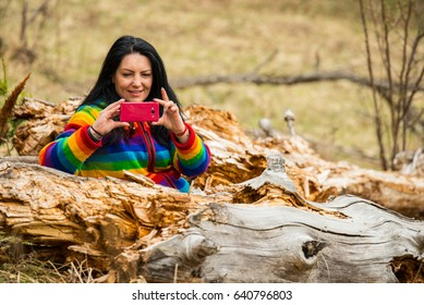 Cheerful woman in nature making a photo with her smartphone