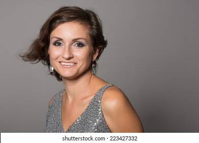 Cheerful woman on a gray background. Woman 36 years old.