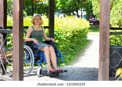 cheerful woman on wheelchair in the park rising smiling and looking to the camera