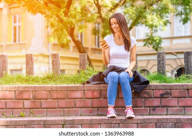 A cheerful woman in a Park using apps and software on her Smartphone.