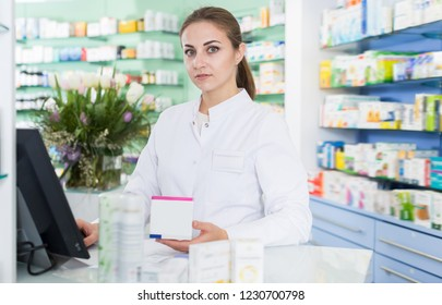 Cheerful woman pharmacist is standing welcoming near cashbox in pharmacy