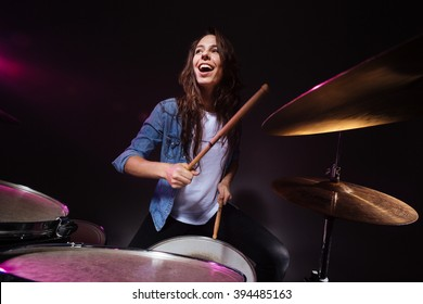 Cheerful woman playing the drums