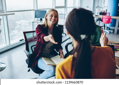 Cheerful woman pointing on female colleague during discussion about business project , skilled crew of women designers satisfied with brainstorming session share creative ideas in coworking office