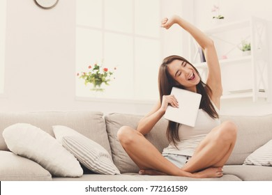 Cheerful woman raising hand while receiving good news on the digital tablet, sitting on couch in light living room. Home, leisure, technology and happiness concept.