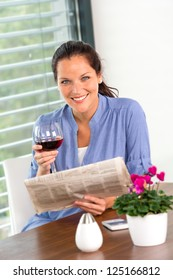 Cheerful woman reading drinking wine newspaper living room