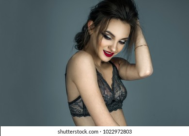 cheerful woman with red lips and beautiful hairstyle posing on camera in lace bra in studio