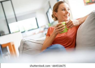Cheerful woman relaxing in sofa and drinking tea