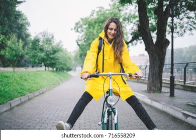 Cheerful woman riding bicycle and wearing yellow raincoat. Young woman cycling in the raincoat