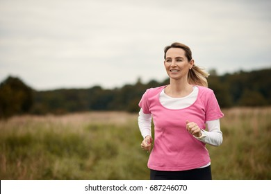 Cheerful woman running through field in fall, copy space to the left
