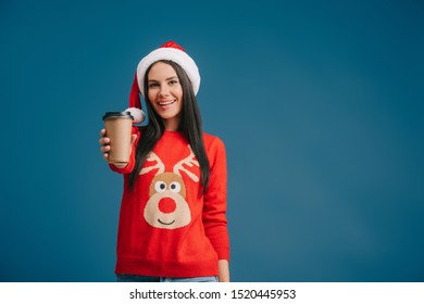cheerful woman in santa hat holding coffee to go, isolated on blue