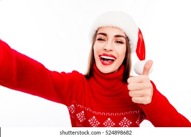 Cheerful woman in santa hat making selfie and showing thumb up