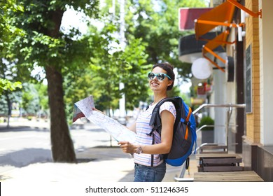 Cheerful woman searching direction on location map while traveling abroad in summer, happy female tourist searching road to hotel on atlas in a foreign city during vacation