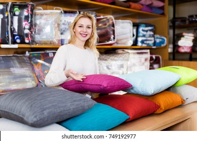 Cheerful woman seller displaying various home textiles in shop