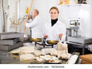 Cheerful woman and senior man workers kipping turron in food manufacture