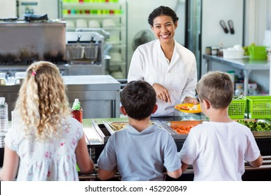 Cheerful woman serving food to schoolchildren in canteen