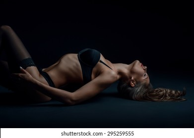 Cheerful woman in sexy clothing is lying on dark surface. She is raising her breast up with passion. Her eyes are closed. Isolated on black background