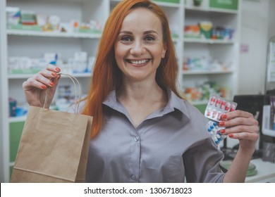 Cheerful woman smiling to the camera, holding shopping bag and blister of pills at the drugstore. Lovely mature woman buying medicine at local pharmacy. Service, health, wellbeing concept