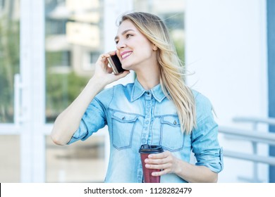 Cheerful woman speaks on the phone and drinks coffee. Concept of life style, urban, work.
