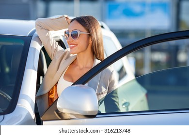 Cheerful woman is standing near her car and relaxing. She is opening the door and looking forward happily. The lady is smiling. She is wearing sunglasses