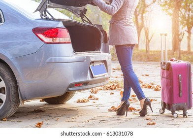 Cheerful woman is standing near her car and closing the trunk. There is a suitcase near her.