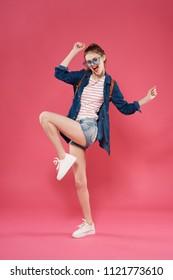 cheerful woman standing on one leg blue shirt shorts