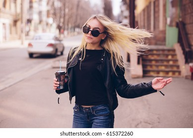 Cheerful woman in the street drinking morning coffee. Coffee to go