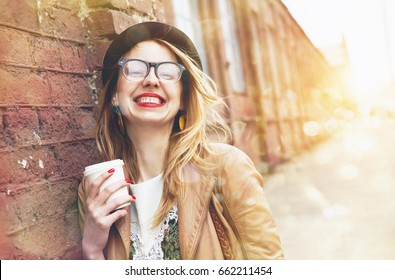 Cheerful woman in the street drinking morning coffee in sunshine light