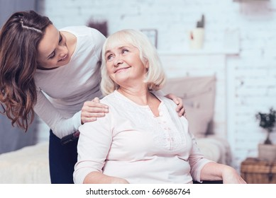 Cheerful woman taking care of her grandmother on wheelchair